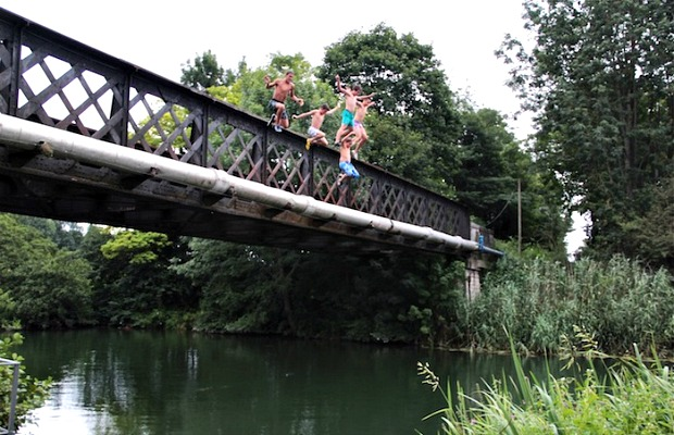 Children dive off a bridge into the water in Dole, France